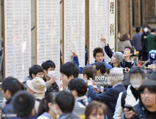 Students flock to the bulletin board at the University of Tokyo's Hongo campus in Tokyo on March 10 to see if they passed the university's entrance...