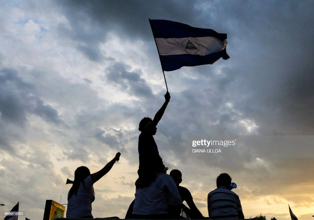TOPSHOT - Students flutter a Nicaraguan national flag as they take part in a protest against the government of Nicaraguan President Daniel Ortega in Managua on May 15, 2018. - Ortega will attend long-awaited crisis talks with the opposition after nearly a month of violence that has left scores dead, officials said Tuesday.