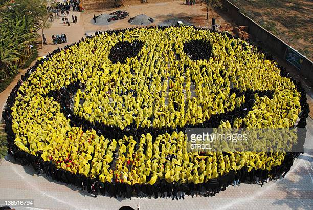 4444 students from 25 schools in Gwalior stand together and form a smiley face by holding coloured cloths in Gwalior on February 8 2012 in an attempt...