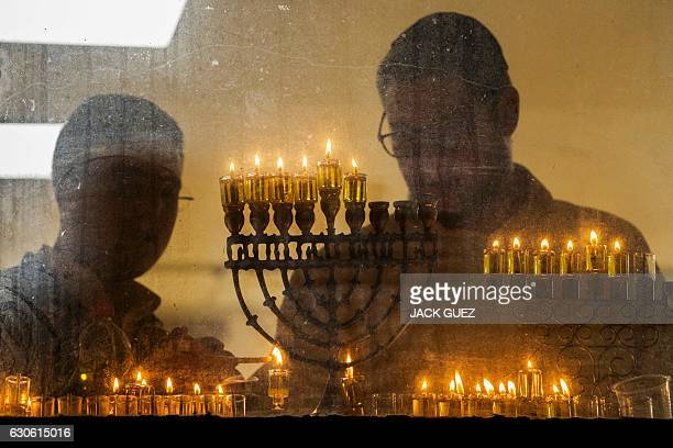 TOPSHOT Students from a Yeshiva religious school light candles on a menorah during the Jewish holiday of Hannukah the festival of lights in the...
