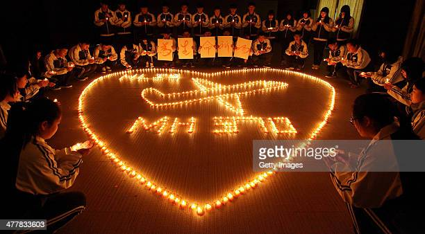 Students from an international school in east China city Zhuji pray for the passengers onboard Malaysia Airlines flight MH370 by lighting candles on...