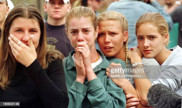 Students from Columbine High School in Littleton CO watch as the last of their fellow students are evacuated from the school building 20 April 1999...