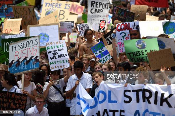 Students from different schools raise placards during a protest rally for climate change awareness at Martin Place in Sydney on November 30 2018...