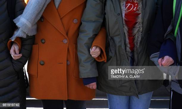 Students from Harvest Collegiate High School form a circle around the fountain in Washington Square Park on March 14 2018 in New York to take part in...