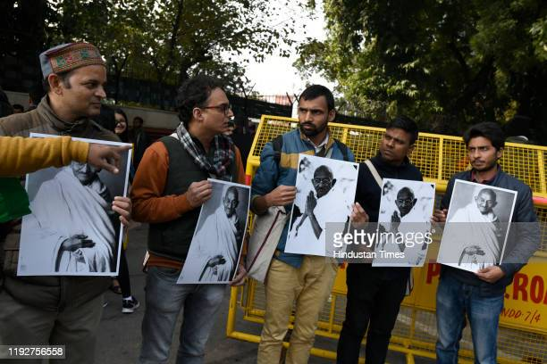 Students from Jawaharlal Nehru University hold photos of Mahatma Gandhi during a protest march from Mandi House to HRD Ministry, demanding the...