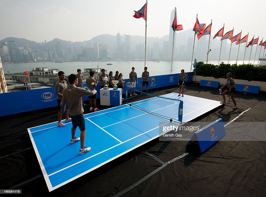 Students from King George the V, ESF School, play tennis for the cameras, next to the AO trophys, over looking the Hong Kong skyline, during the Australian Open Trophy tour on October 22, 2013 in Hong Kong, Hong Kong.