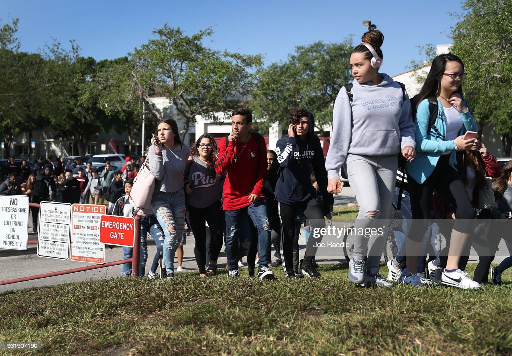 Students from Marjory Stoneman Douglas High School walk out of school to honor the memories of 17 classmates that were killed during a mass shooting at the school on March 14, 2018 in Parkland, Florida. The students joined others around the country to mark the one month anniversary of the shooting with a National Walk out day.