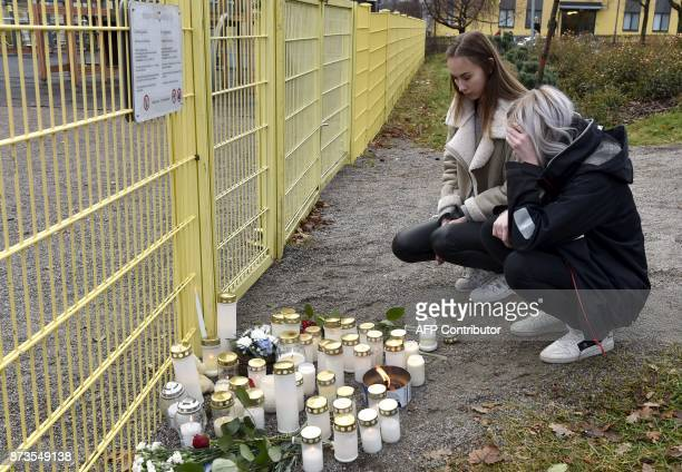 Students from Porvoo high school Amanda Raunio and Cassandra Flykt look at the memorial candles next to the childen's playground where a man stabbed...