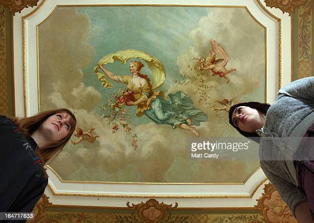 Students from Swansea Metropolitan University Rosie Cook and Emily Cryer look up to a fresco by artist Thomas WallaceHay which is on display for the...