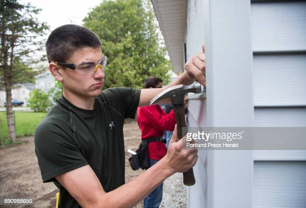 Students from the Biddeford Center of Technology renovated an abandoned house with help from the local Rotary Club Junior Joe Gamage nails siding...