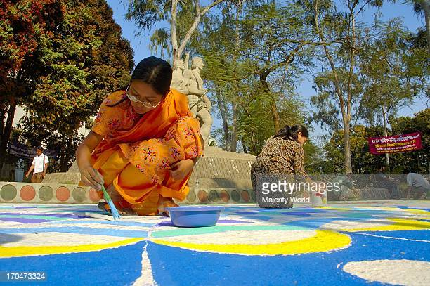Students from the Fine Arts Institute of Dhaka University paints floral motifs in front of Oporajeo Bangla at Dhaka University in celebration of...