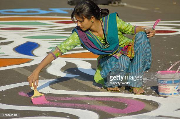 Students from the Fine Arts Institute of Dhaka University paints floral motifs on the road infront of Central Shahid Minar a monument for the martyrs...