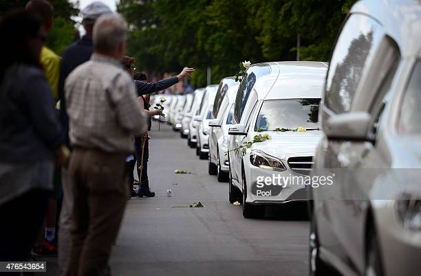 Students from the Joseph-Koenig-Gymnasium high school watch as hearses carrying the remains of 16 of their fellow students and two teachers who were...