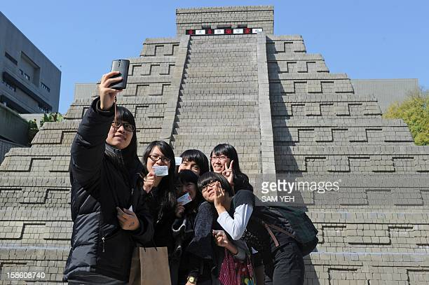 Students from the middle school cheer in front of a replica of a Mayan pyramid before a countdown ceremony organized by the National Museum of...