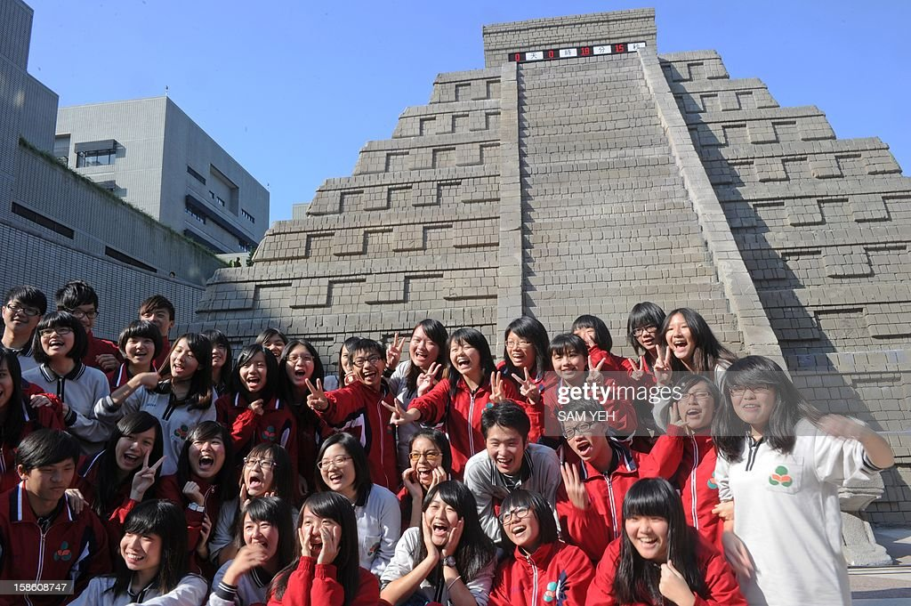 Students from the middle school cheer in front of a replica of a Mayan pyramid before a count-down ceremony organized by the National Museum of Natural Science to help ensure the public it is not the end of the world, in central Taichung on December 21, 2012. A digital 'doomsday clock' on top of a two-storey replica Mayan pyramid erected at a museum in central Taiwan's Taichung city completed its countdown for the end of the world at 0600 GMT -- midnight in Mexico. AFP PHOTO / Sam Yeh