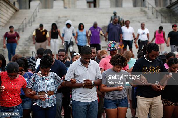 Students from the University of South Carolina and South Carolina State University link arms during a moment of silence for the nine victims of last...