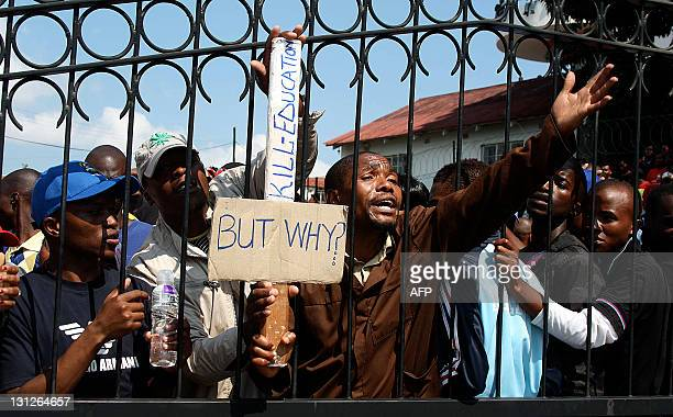 Students from the University of Swaziland, locked inside their University ask police officers to let them out during a protest in Mbabane on November...
