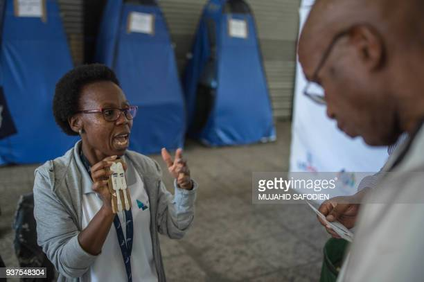 Students from the University of the Witwatersrand explain the self HIV testing kit in Hillbrow Johannesburg on March 19 2018 Selftesting kits and...
