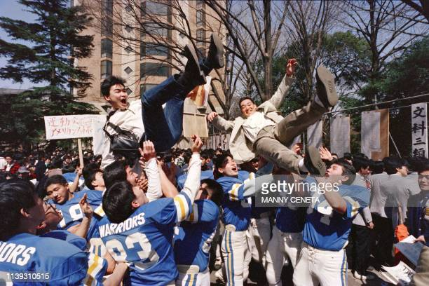 Students from Tokyo University, the most prestigious in the country, toss to welcome newcomers in the air on March 21, 1989 after receiving the...