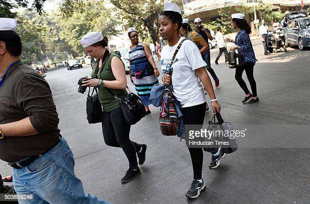 Students from USA deliver tiffin boxes to customers as they spend a day with the Mumbai Dabbawalas trying to decode their delivery management at...