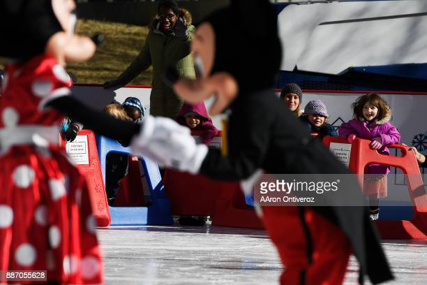 Students from Warren Village Learning Center react to the arrival of Mickey and Minnie Mouse at the Downtown Denver Rink at Skyline Park on Wednesday...