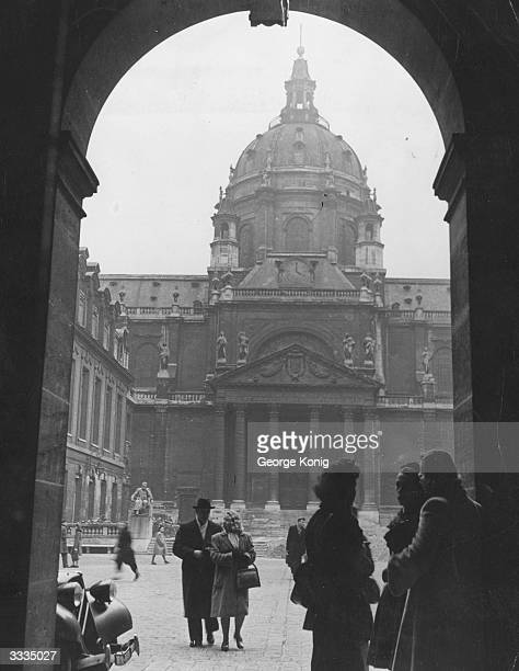 Students gather at the entrance to the main courtyard of the Sorbonne Paris Statues of historical French figures look down on the scene
