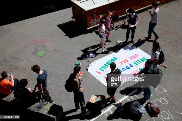 """Students gather in a yard around a banner reading """" is too beautiful to become a trash bin"""" in a building occupied by students at Saint-Denis..."""