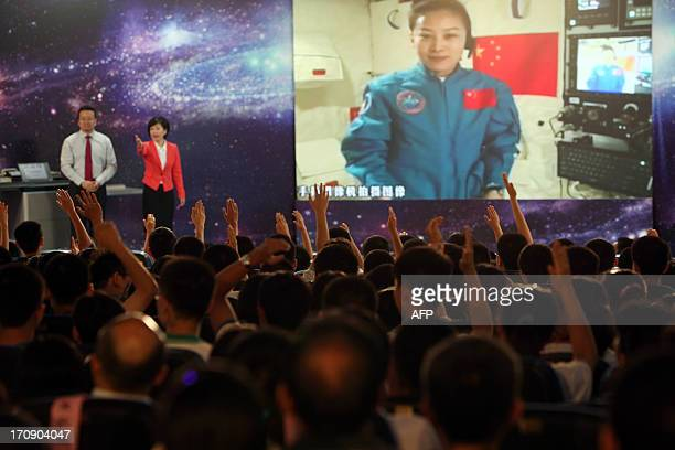Students gathered in a school in Beijing raise their hands to ask Chinese female astrounaut Wang Yaping questions as she delivers a lesson to them...