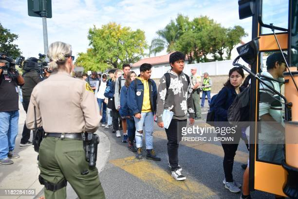 Students get on a bus after a shooting at Saugus High School in Santa Clarita California on November 14 2019 At least four people were injured in a...