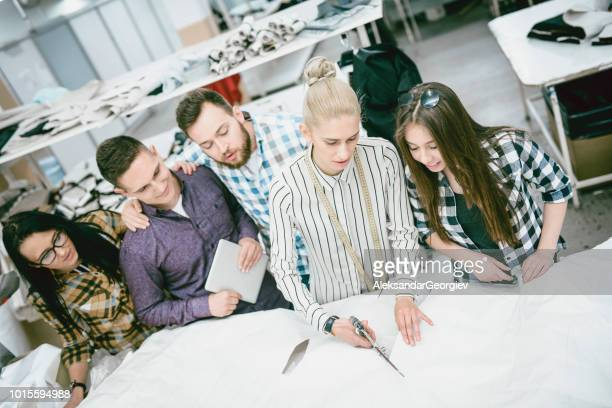 Students Getting A Lesson In Correct Cutting By Textile Engineer