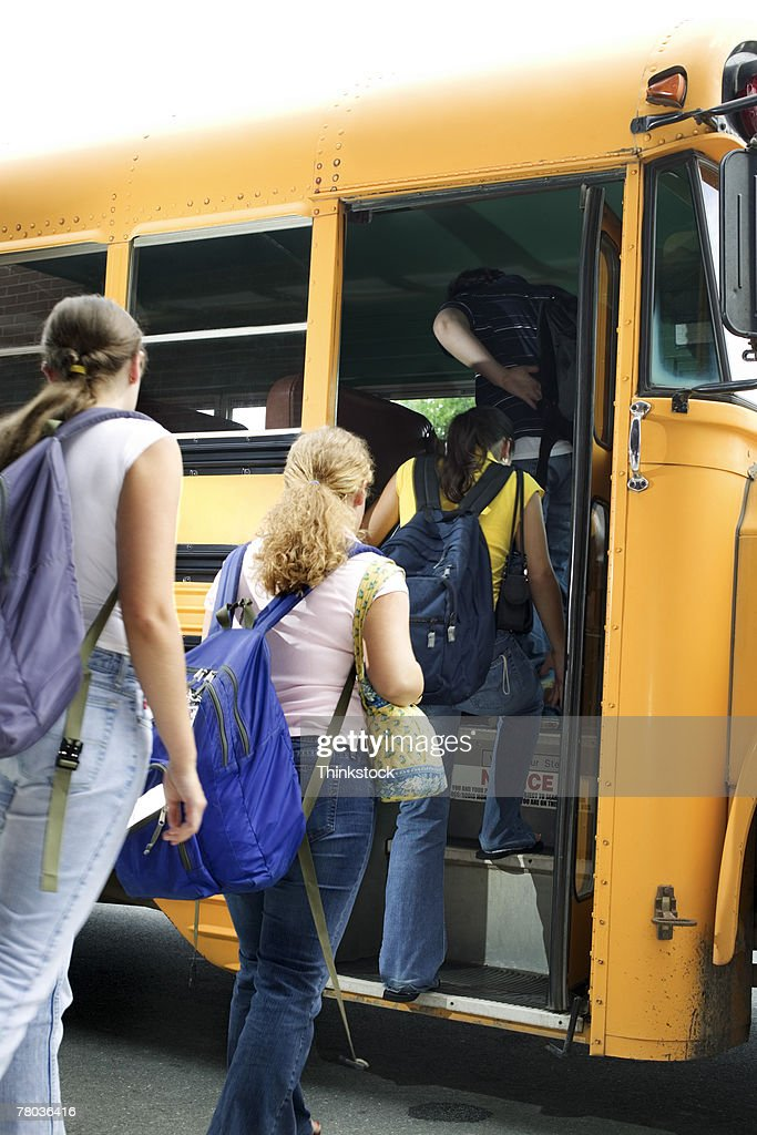 Students getting on school bus : Stock Photo