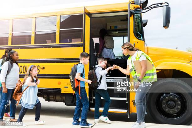 students give fist bumps to bus driver - school bus stock pictures, royalty-free photos & images