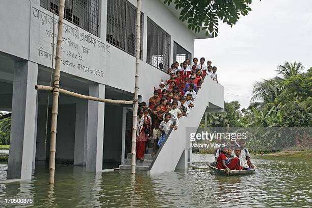 Students go home by boat after school during flood at Bhagna area under Keraniganj Dhaka Bangladesh August 1 2007