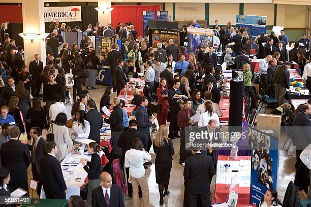 Students graduates and adults seeking job opportunities gather around tables of corporations and government offices during a job fair at Rutgers...