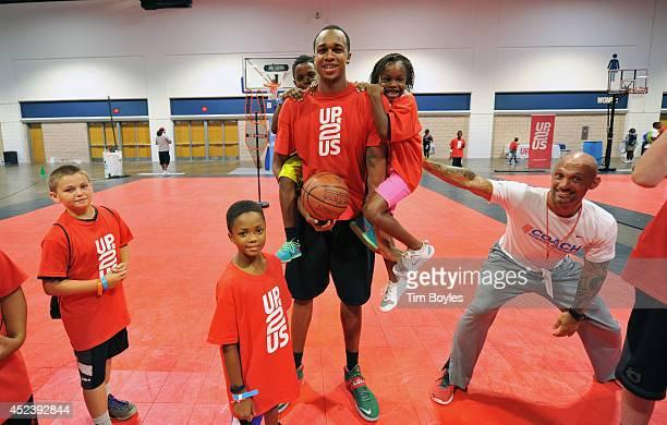 Students hang on Milwaukee Bucks forward John Henson at the John Henson Experience benefitting Up2Us at the Tampa Bay Youth Sports Expo on July 19...