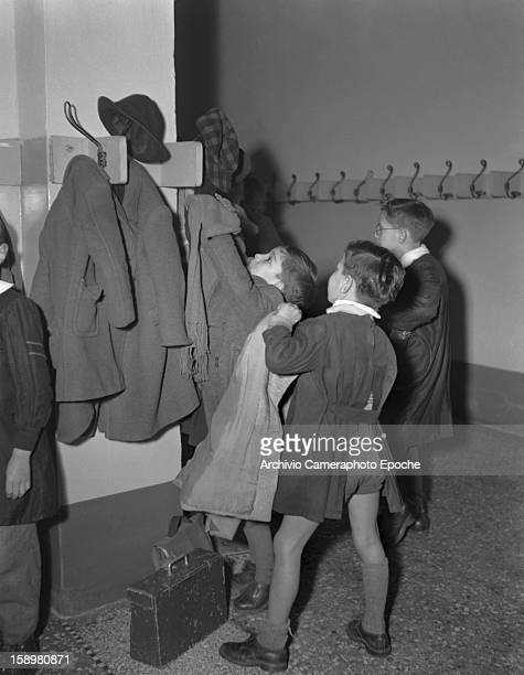 Students hang their coats arrive at an unidentified boys' school Venice Italy 1949