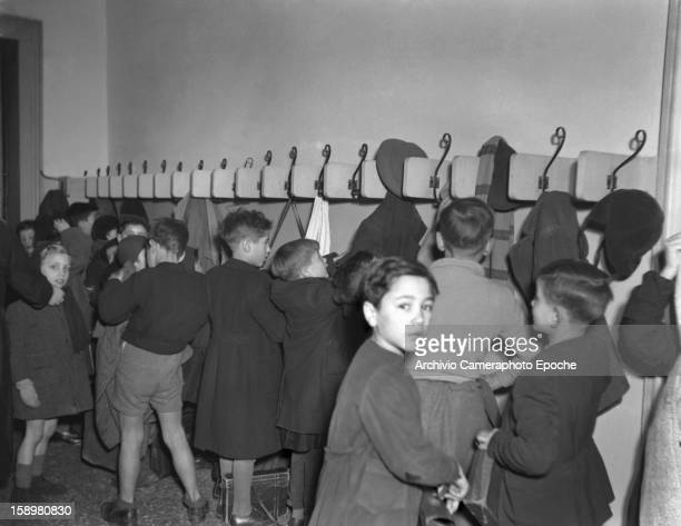 Students hang their coats as they arrive at an unidentified boys' school Venice Italy 1949