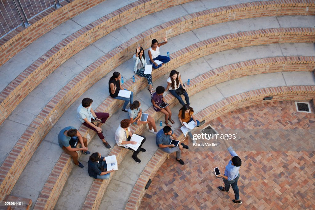 Students having class in outside auditorium : Stock Photo