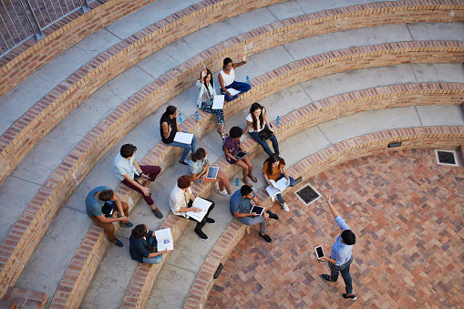 Students having class in outside auditorium - gettyimageskorea