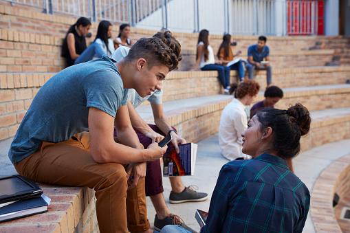 Students having conversation in auditorium - gettyimageskorea