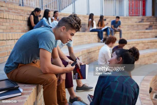 Students having conversation in auditorium