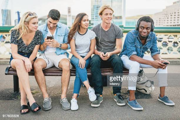 students having fun sitting together on bench - darling harbour stock pictures, royalty-free photos & images