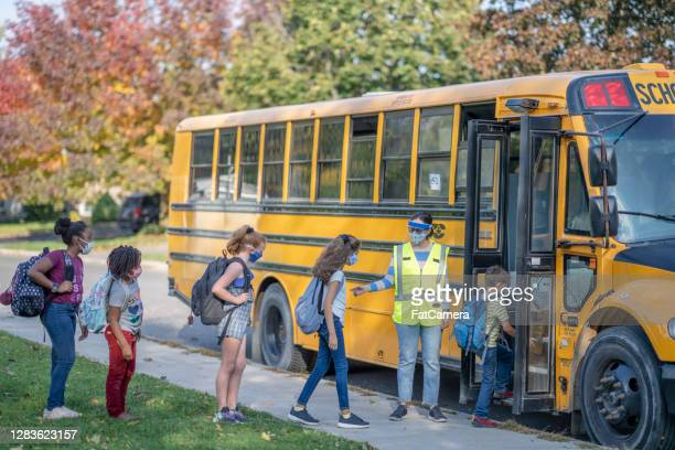 students heading to school wearing masks - school bus stock pictures, royalty-free photos & images