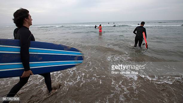 MALIBU CA MARCH 11 2015 Students hit the surf after Pepperdine's Wednesday morning Surf Chapel on Zuma Beach March 11 2015 in Malibu