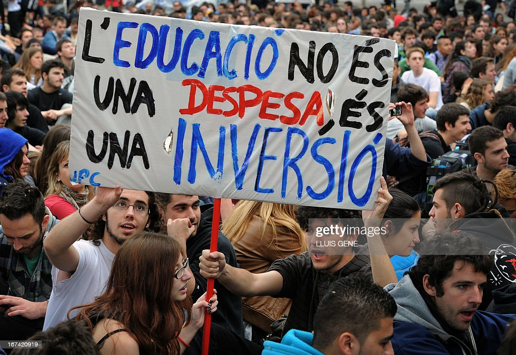 Students hold a banner reading in Catalan 'The education is not an expense, it is an investment' during a demonstration against the government's cuts to education spending in Barcelona on April 25, 2013.