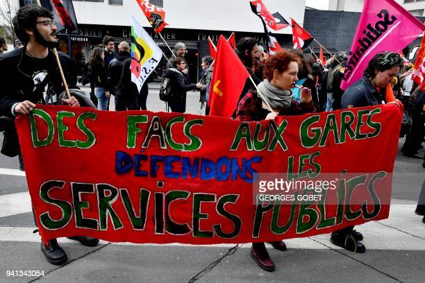 Students hold a banner reading 'Universities to the trains stations Let's defend public service' as they joint a protest rally in Bordeaux...
