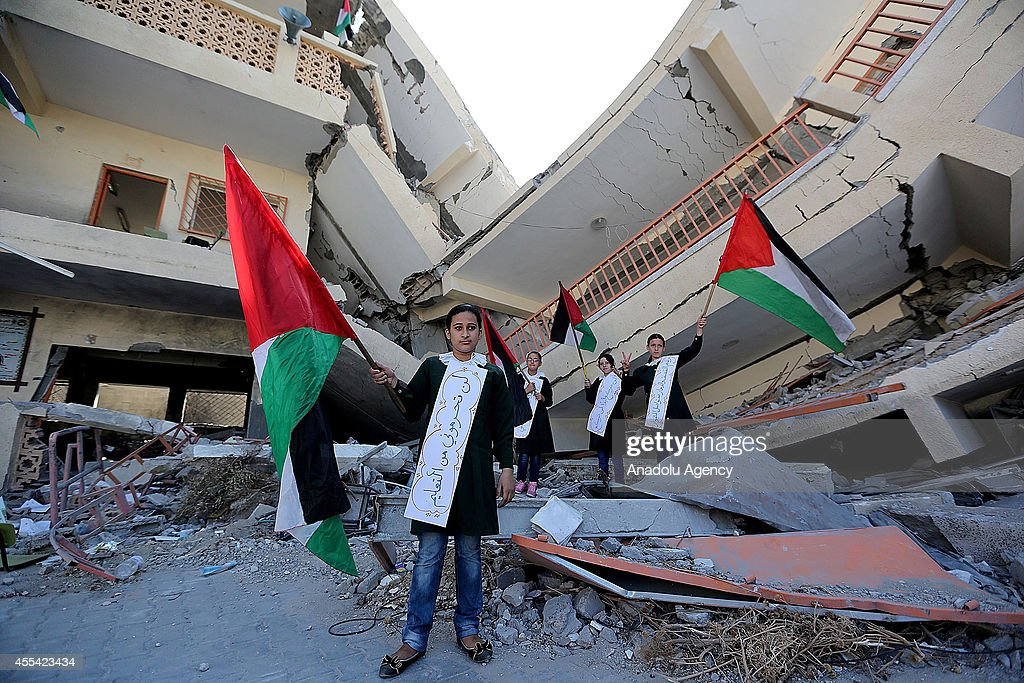 Students hold a Palestinian flag as they listen to Palestinian deputy minister of education Ziyad Sabid's (Not seen) speech on the first day of the new school year at Shujaya Martyrs Primary School in Gaza City, Gaza on September 14, 2014.