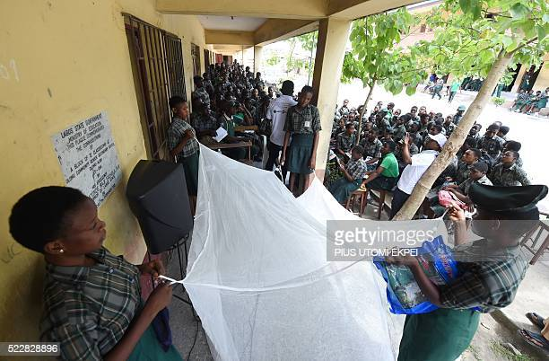 Students hold a treated mosquito net during a malaria prevention action at Ajah in Eti Osa East district of Lagos on April 21 2016 Dozens of patients...