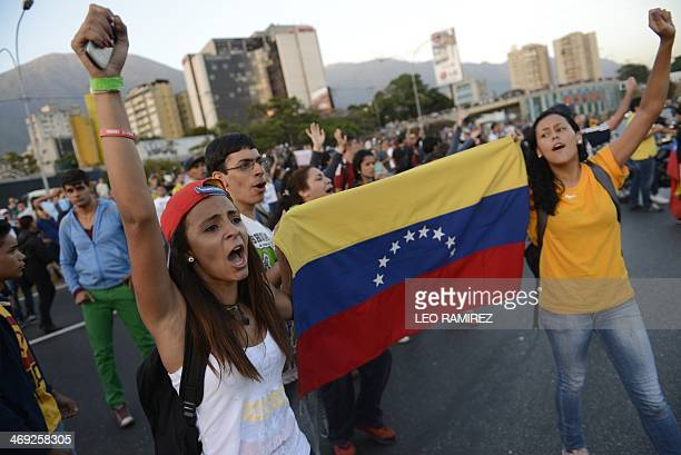 Students hold a Venezuelan national flag as they protest against the government of Venezuelan President Nicolas Maduro aklong a main highway in...