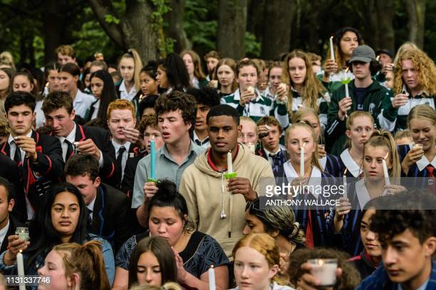 Students hold candles during a vigil in Christchurch on March 18 three days after a shooting incident at two mosques in the city that claimed the...